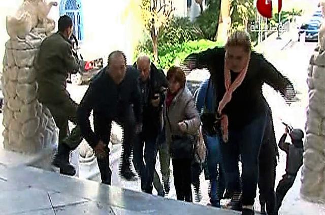 18日、武装グループに襲撃されたバルドー博物館から逃げる人たち(国営放送のチュニジア1の映像から)=AFP時事