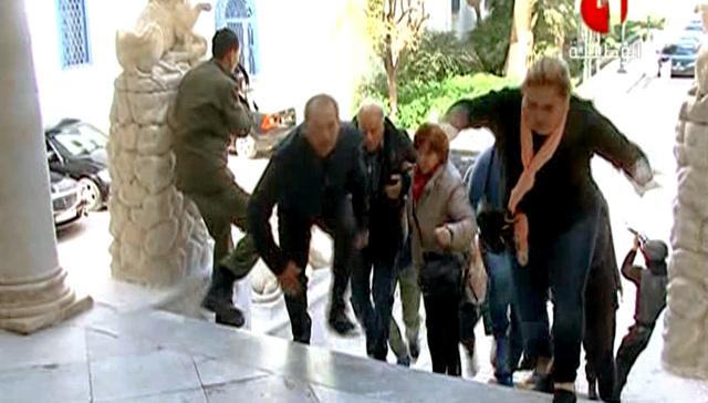 18日、チュニジアの首都チュニスで、武装勢力に襲撃された国立バルドー博物館から逃げる人々(国営放送のチュニジア1の映像から)=AFP時事