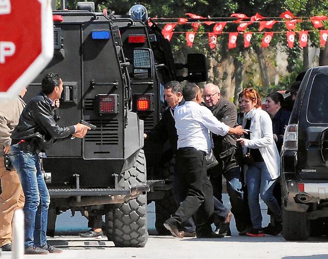 チュニジアの首都チュニスで18日、襲撃されたバルドー博物館から避難する観光客=AFP時事