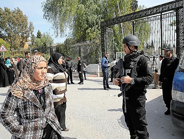 チュニスで19日、襲撃から一夜明けたバルドー博物館を警備する警察官=AP