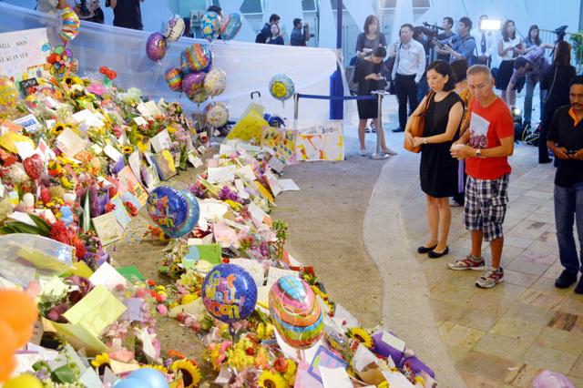 リー・クアンユー氏が入院していたシンガポール総合病院に設置された献花台の前で、リー氏の死を悼む人たち=23日午前、シンガポール、都留悦史撮影