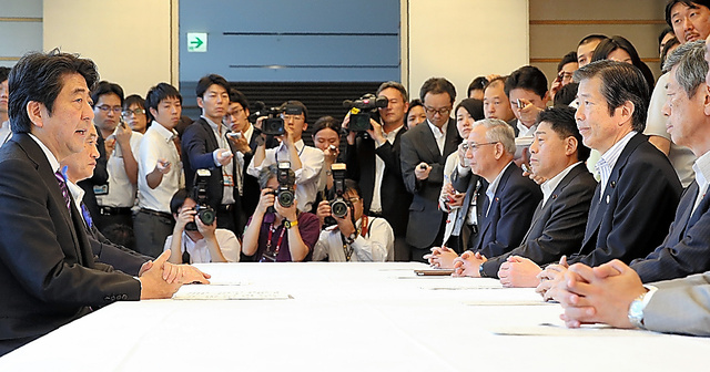2014年7月1日、安倍首相(左)に閣議決定の文案で合意したことを報告する自民、公明の幹部(右)=首相官邸