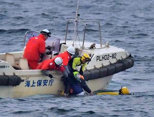 転覆した第18明祐の船内から救助され、海上保安庁の船に引きあげられる永田勝行さん=28日午前5時55分、北海道函館市、恵原弘太郎撮影