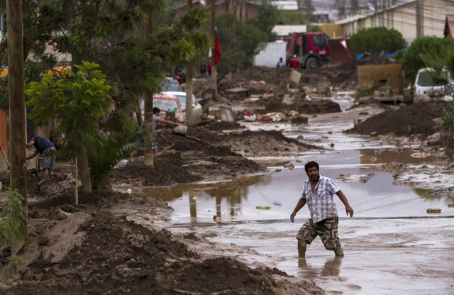 チリ北部のコピアポで30日、大雨で冠水した道路を歩く男性=AFP時事