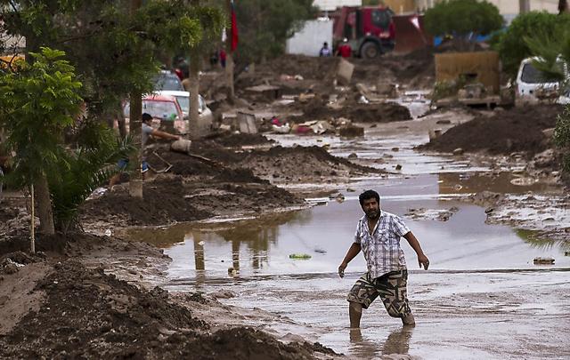 チリのコピアポで30日、冠水した道路を歩く男性=AFP時事