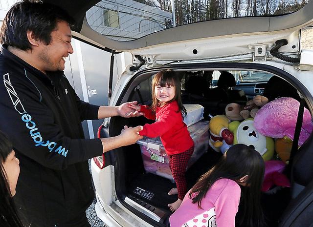 仮設住宅から衣類を運び出し、帰還の準備をする坪井秀幸さん(左)。娘たちも自分たちのぬいぐるみを車に積み込む手伝いをしていた=3月28日午後、福島県田村市、杉本康弘撮影