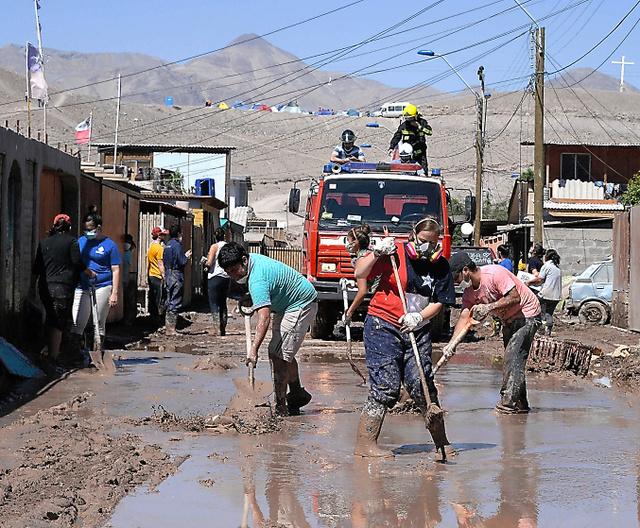 豪雨による洪水で積もった泥をかき出す住民ら=4日、チリのアタカマ州、田村剛撮影
