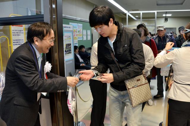 「カムサハムニダ(ありがとう)」などと言いながらソウル便の搭乗客に記念品を手渡す三村申吾知事(左)=3日、青森市大谷の青森空港