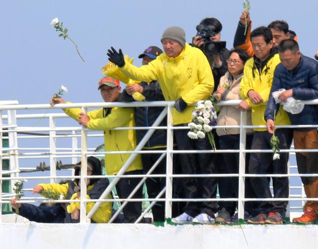 韓国旅客船セウォル号沈没事故から16日で1年を迎えるのを前に事故海域をフェリーで訪れ、花を海に捧げる遺族たち=15日午前10時49分、韓国・珍島沖、東岡徹撮影