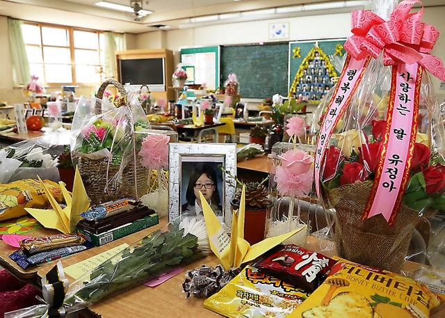 生徒たちが使っていた机の上には写真やメッセージ、花が供えられている=いずれも4日、東岡徹撮影