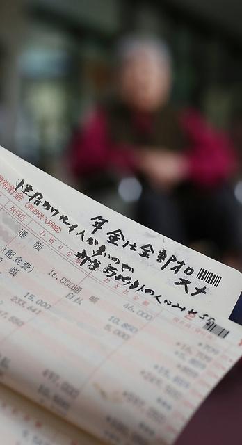 娘婿に年金を使われ続けていた頃の90歳女性(後方)の通帳には「年金は全部オロスナ」などの走り書きがあった(明細の一部にモザイクをかけています)=福岡県内、河合真人撮影