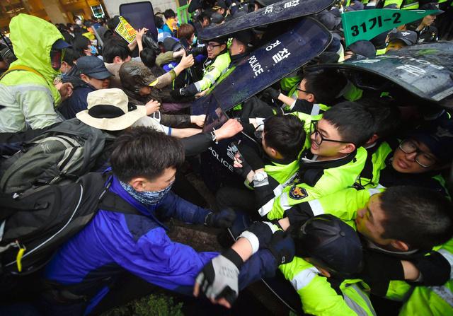 ソウルで18日、警官隊(右手)と激しくもみ合う旅客船セウォル号沈没事故の追悼集会の参加者ら=AFP