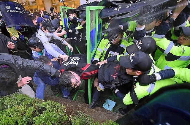 ソウルで18日、警官隊と激しく衝突する追悼集会の参加者ら=AFP時事