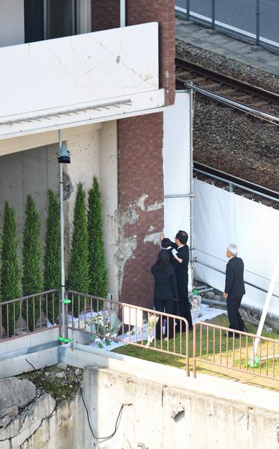 電車が衝突した事故現場の壁にそっと手を添え追悼する人たち=25日午前9時21分、兵庫県尼崎市、遠藤真梨撮影