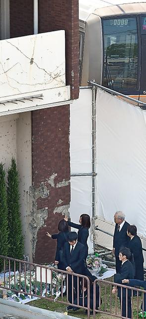 電車が衝突した事故現場の壁にそっと手を添え追悼する人たち=25日午後0時10分、兵庫県尼崎市、遠藤真梨撮影