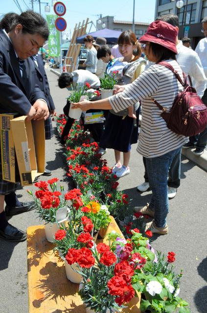 高校生が育てた花を買い求める家族連れら=矢板市本町