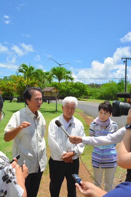オスプレイの事故があった基地を背に取材に応じる沖縄県議=27日、米ハワイ州、泗水康信撮影