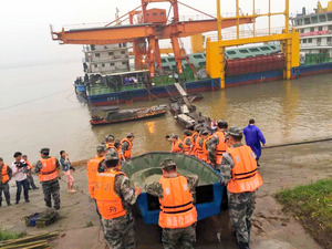 中国・湖北省を流れる長江で2日、転覆した客船を捜索するためボートを運ぶ救助隊員ら=ロイター