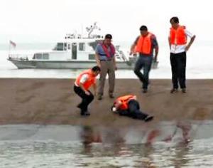 転覆した船底をたたき、中に生存者がいるかどうか確認する救助隊=中国国営中央テレビのニュースから