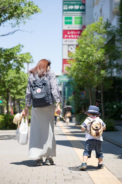 安全のため、リードをつけて一緒に街を歩く親子=東京都世田谷区、山口明夏撮影