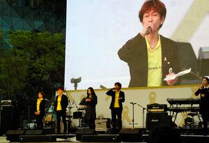 旅客船セウォル号沈没事故から1年を迎えた4月16日、ソウルで開かれた追悼行事で、自ら作詞した歌を紹介する上林英夫さん=東岡徹撮影