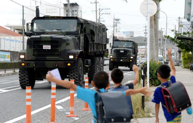 街なかを走る米軍車両は沖縄の日常風景だ。下校途中の子供たちが手を振っていた=沖縄県宜野座村、諫山卓弥撮影