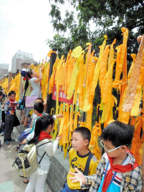 客船が転覆した荊州市監利県にある小学校の柵には、乗客の無事を願い、犠牲者を悼むメッセージを書いた黄色いリボンが結ばれていた=5日、金順姫撮影