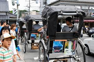 観光客で混雑するなか、いくつかの業者が人力車を走らせている=神奈川県鎌倉市