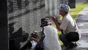 「平和の礎」に刻まれた名前に向かい、手を合わせる遺族たち
