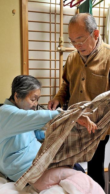 母・善子さん(左)を寝かせるため、エプロンを外す中西義一さん=大津市、仙波理撮影