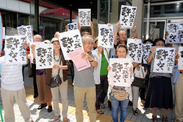 「アベ政治を許さない」というポスターを掲げる人たち=津駅前