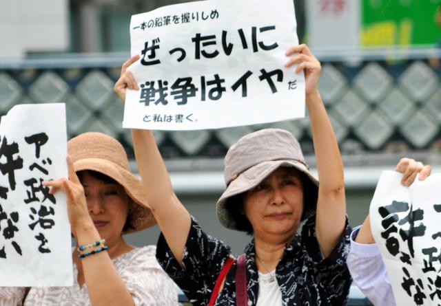自作のスローガンを掲げる荒木紀理子さん=川口市