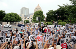 コンビニなどで印刷した共通のメッセージを国会前で掲げる人たち=18日午後1時3分、嶋田達也撮影