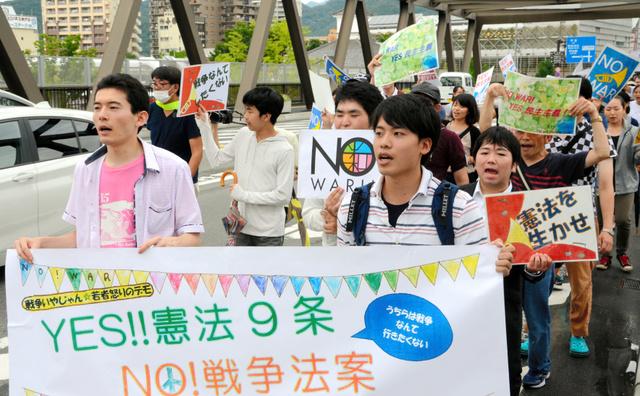軽快なリズムに乗せて「強行採決絶対反対」などとコールを上げるデモ参加者=JR甲府駅前