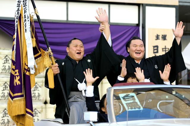 優勝パレードで白鵬(右)に手を上げられ、笑顔を見せる旭天鵬=26日午後、名古屋市の愛知県体育館、小宮路勝撮影