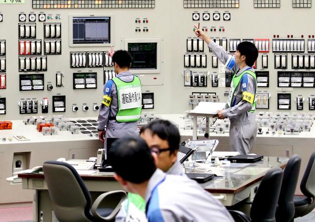 九州電力川内原発1号機の中央制御室で原子炉の起動操作をする作業員ら=11日午前10時30分、鹿児島県薩摩川内市、代表撮影