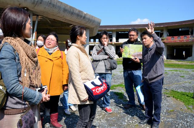 被災校舎の前で見学者に説明をする佐藤敏郎さん(右端)。学校で妻と長女を亡くした只野英昭さん(右から2人目)も一緒に語った=宮城県石巻市