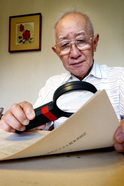 ルーペを使って戦争神経症の古い資料に目を通す目黒克己=東京都国分寺市、鬼室黎撮影