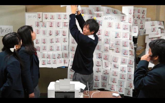 「三」の文字を重ね合わせた紙を印刷し、ホワイトボードにはって検証作業をする生徒たち=岐阜工業高校提供