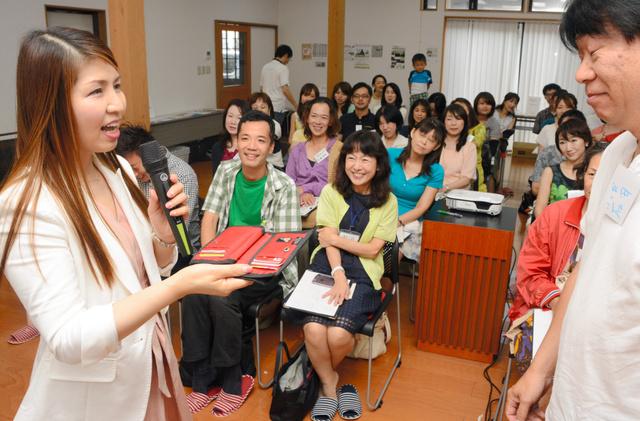 参加者の財布を手にコメントする佳山知未さん(左)=富山市金泉寺