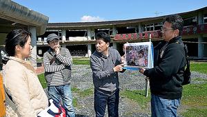 被災校舎の前で、遺族の只野英昭さん(右端)とともに見学者に説明する佐藤さん(右から2人目)=宮城県石巻市