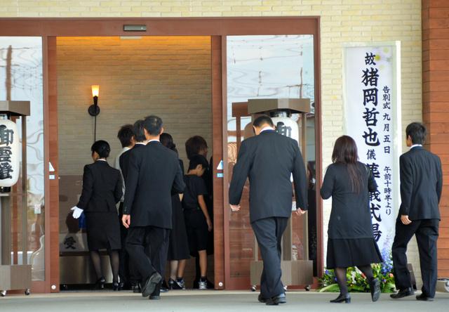 猪岡哲也さんの葬儀に参列する人々=甲斐市竜地