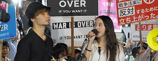 安保関連法案に反対し、ステージ上で声を上げる津田塾大2年の女性(右)と奥田愛基さん=11日午後8時36分、国会前