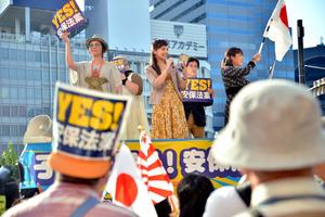 「YES!安保法案」と書かれたプラカードや日の丸の旗を掲げる参加者たち=東京都新宿区