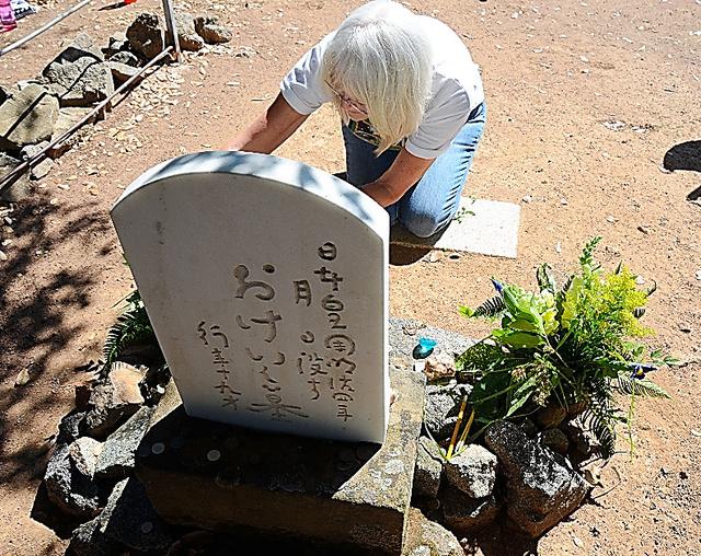 「おけい」の墓に花を手向けるボランティア=米カリフォルニア州プラサビル