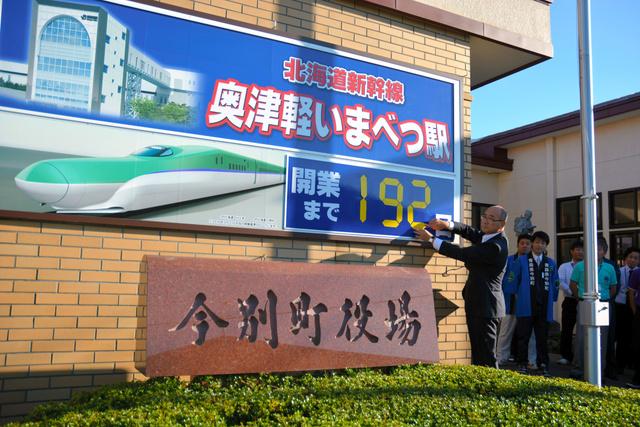 197日だった開業までの数字を192日に変更する阿部義治町長(左)=青森県今別町
