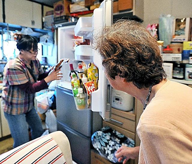 冷蔵庫の食料品を整理する介護事業所の中本嘉子さん(奥)。捨てるかどうか女性に一つずつ確かめる=埼玉県、仙波理撮影