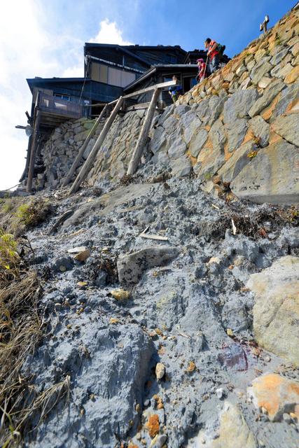 御嶽山の9合目付近。登山道の脇にはまだ火山灰の塊が残る。奥は「石室山荘」=19日正午、木曽町、小川智撮影