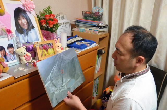 長山照利さんの父、幸嗣さん。照利さんの遺影の前で、御嶽山を上空から写した写真を手にして当時の状況を語った=愛知県豊田市