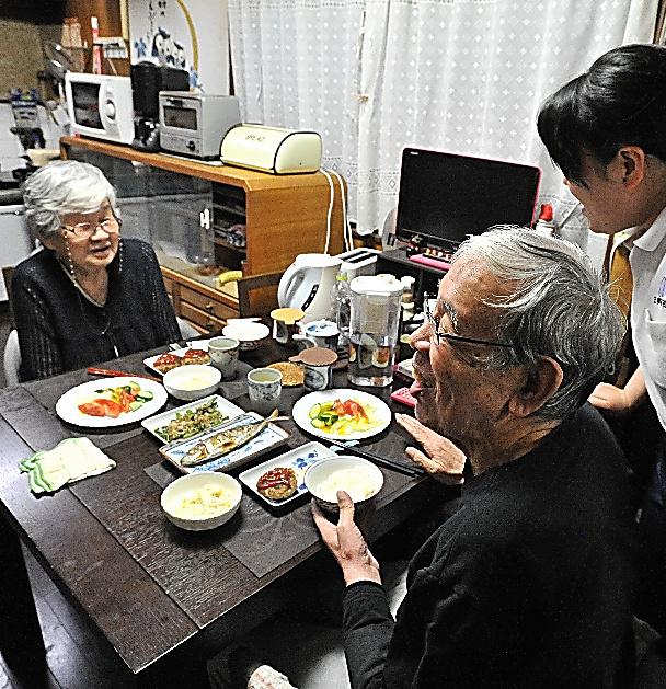 薫子さん(奥)とヘルパー(右端)が一緒に作った夕食を囲む。博之さんはハンバーグに大喜び=大阪府、仙波理撮影